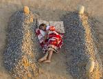 enfant dort entre la tombe de son pere et de sa mere